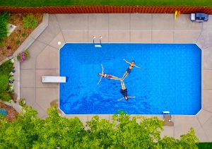 aerial view of swimming pool, garden, and three girls playing