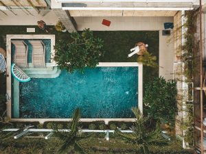 aerial view of backyard oasis swimming pool and two men