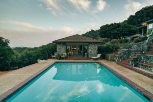 mountainside swimming pool with pool house
