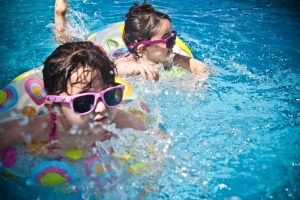 2 little girls in sunglasses swimming with pool rings