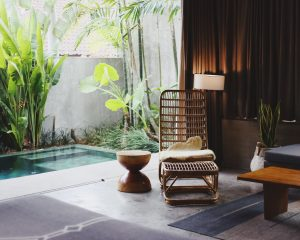 small backyard oasis lap pool with rattan chair poolside