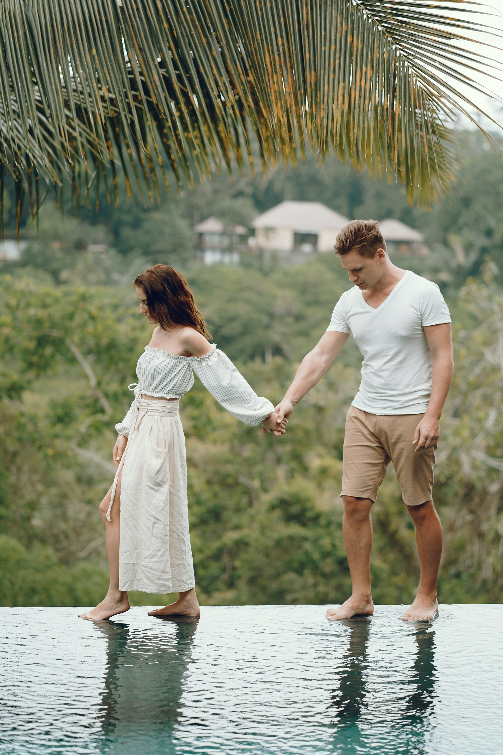 relaxed couple holding hands on swimming pool edge 4172886 scaled